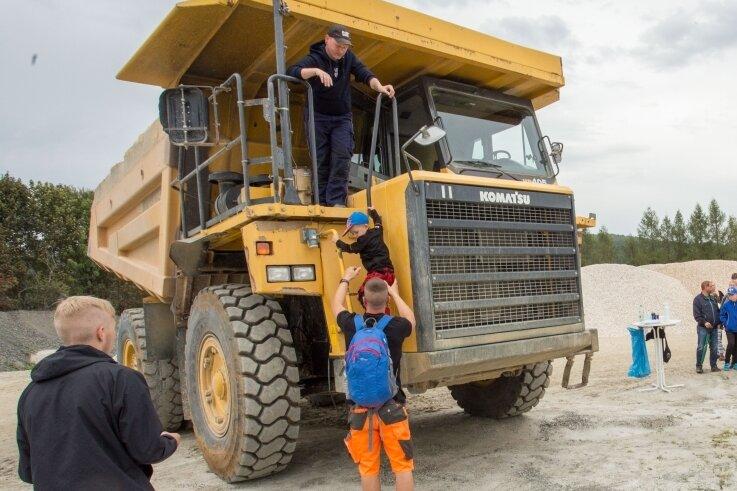 Christian Lorenz und der kleine Collin klettern aus dem 40 Tonnen schweren Muldenkipper.