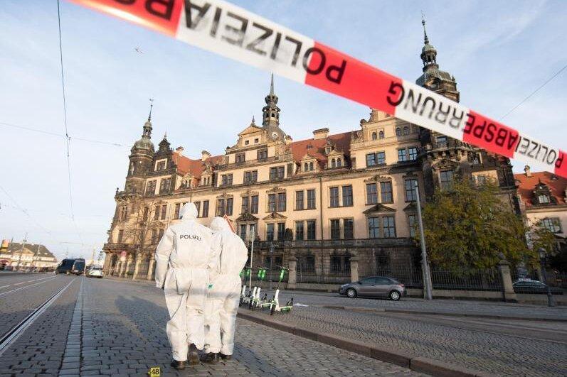 Zwei Mitarbeiter der Spurensicherung stehen im November 2019 vor dem Dresdner Residenzschloss mit dem Grünen Gewölbe hinter einem Absperrband.