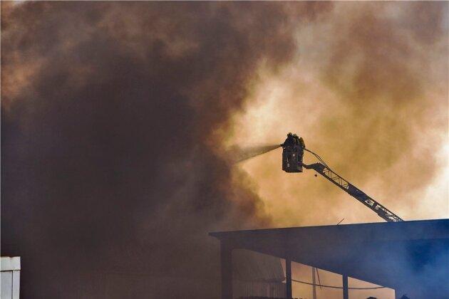 Harte Arbeit an der Quelle der riesigen, über die Region wehenden Rauchfahne. Über in die Wand der Halle gerissene Löcher gelang es der Feuerwehr schließlich von zwei Drehleitern aus, das Feuer einzudämmen und zu löschen.