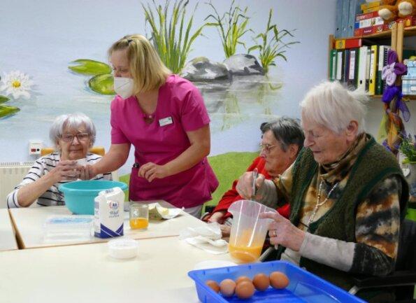 Unter Anleitung von Ergotherapeutin Annika Grimm backen Bewohner des Seniorenzentrums Zschopau einen Kuchen. Ruth Lorek (rechts) kümmert sich ums Schlagen der Eier.