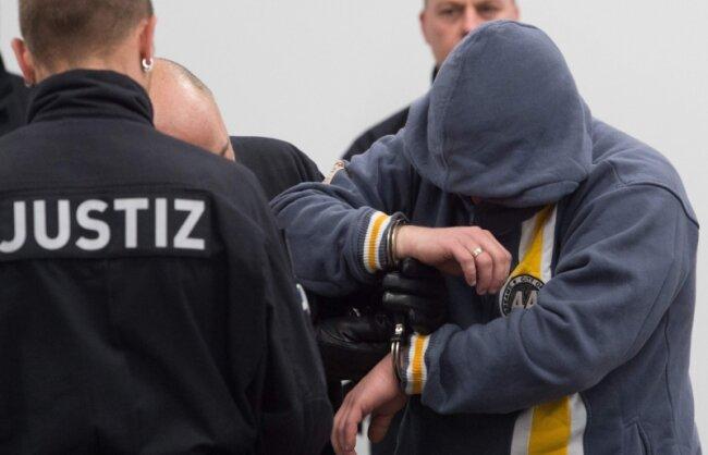Der angeklagte Mike S. kurz vor Prozessbeginn. Er gehörte zu den drei der acht Angeklagten, die ihr Gesicht vor den Fotografen schützten.