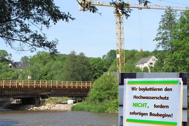 Während die Arbeiten an der Landbrücke zügig voranschreiten, wird in der Dresdner Straße in Niederwiesa mit Protestplakaten gefordert, dass auch der Neubau sowohl der Ufermauer als auch der Deichanlage in Angriff genommen wird.