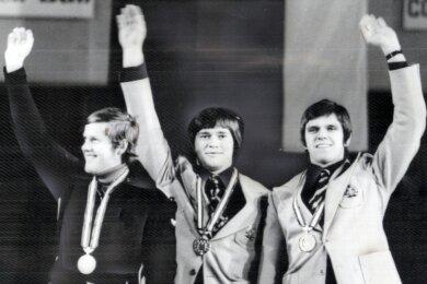 Dettlef Günther (M.) bei der Siegerehrung der Olympischen Spiele 1976 in Innsbruck. Mit ihm auf dem Siegerpodest im Einsitzer-Rodeln der Männer: Hans Rinn (DDR, r., Bronze) und Josef Fendt (BRD, l., Silber).