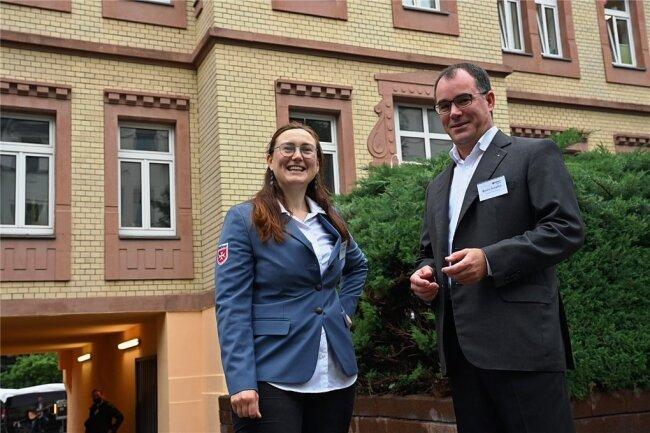 Almut Mighri, die Chemnitzer Leiterin des Malteser Hilfsdienstes, und Propst Benno Schäffel von der katholischen Pfarrei Heilige Mutter Teresa in Chemnitz vor der neuen Dienststelle der Malteser an der Münchner Straße.