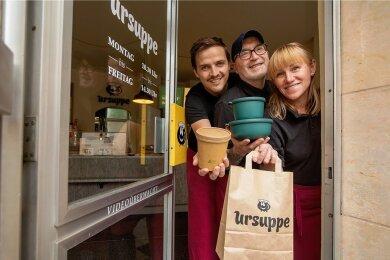 """Mit Inkrafttreten der 3G-Regel hat die """"Ursuppe"""" in Plauen den Restaurantbetrieb wieder eingestellt. Das Essen kann aber nachhaltig verpackt bei Christopher Eichler, Mick McSorley und Larisa Oberhauser (von links) abgeholt werden."""