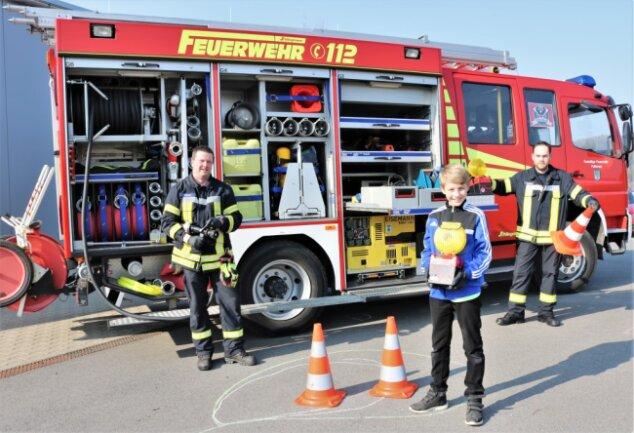 Kamerad Sven Stenker (l.) und der stellvertretende  Wehrleiter Bjön Bork (r.) von der Freiwilligen Feuerwehr Falkenau  zeigten dem elfjährigen Tyler Tanneberger (M.) das Feuerwehrdepot und  die Fahrzeuge.