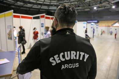 Ein Security-Mitarbeiter überwacht das Geschehen in der Stadthalle Zwickau, die zum Impfzentrum umfunktioniert wurde.