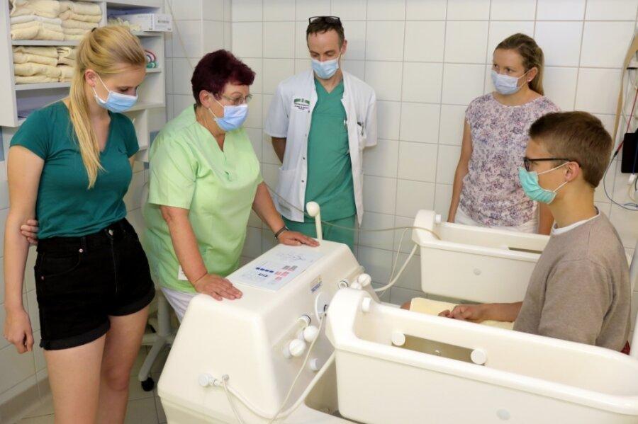 Henriette Zimmeck (l.), Leonhard Schwager und Carolin Specht (v. r.) ließen sich von Mediziner Mathias Baldauf durch die Kliniken Erlabrunn führen. Hier erklärt Ulla Richter von der Physiotherapie das Vier-Zellen-Bad.