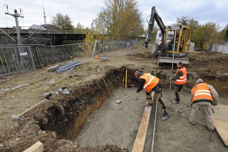 """<p class=""""artikelinhalt"""">Mitarbeiter der Arlt Bauunternehmen GmbH aus Frankenhain bereiten das Fundament für die Behelfsbrücke vor, die für Fußgänger geschaffen wird. Im Hintergrund die Brücke, die abgerissen wird. </p>"""