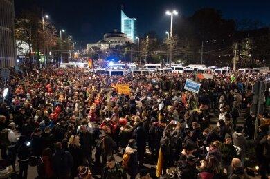 Teilnehmer stehen nach der letzten Demo umgeben von Einsatzfahrzeugen der Polizei am Leipziger Hauptbahnhof.