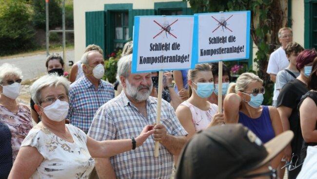 Anwohner fordern während der Dreharbeiten am Montagnachmittag vor der Niederen Mühle im Wildenfelser Ortsteil Schönau auf Plakaten die Schließung der Kompostieranlage.