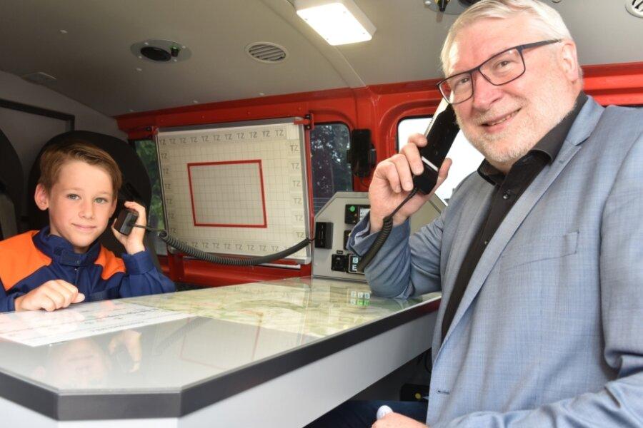 Landrat Matthias Damm hat mit dem achtjährigen Finn Fiedler von der Jugendfeuerwehr Böhrigen/Striegistal Platz genommen und testet am Tisch des Führungspersonals im neuen Einsatzfahrzeug die Kommunikationsmittel. Dazu gehören Telefon und Computer mit Internetverbindung.