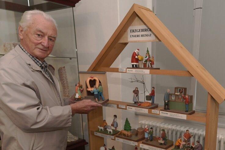 Schnitzlehrer Walter Pflugbeil mit einem Exponat der Sonderschau, das das Erzgebirge im Jahreskreis zeigt.