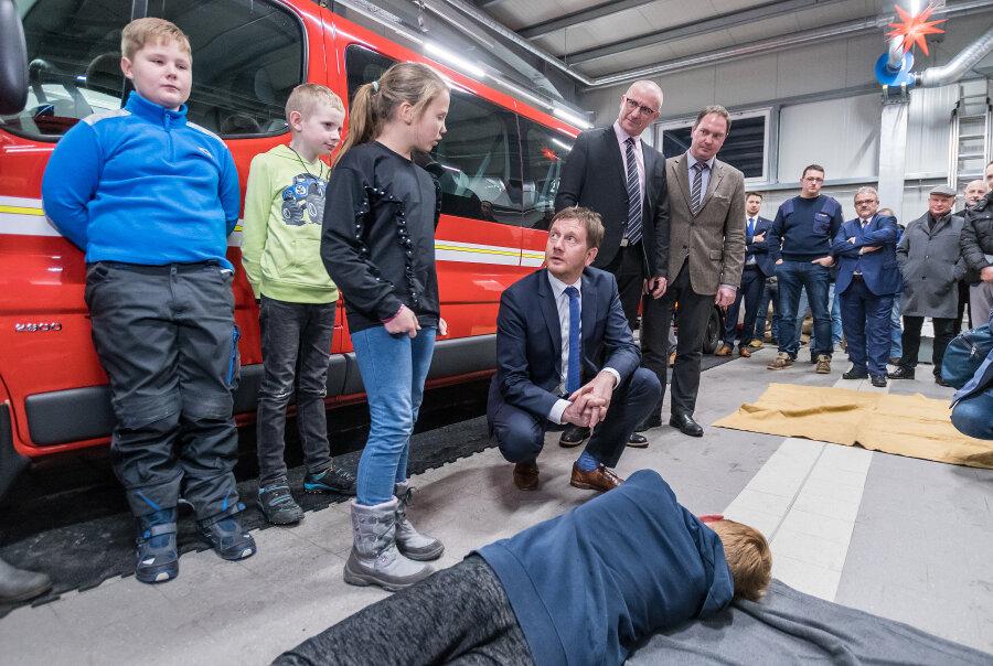 Im Gerätehaus der Freiwilligen Feuerwehr Kühnhaide ließ sich Ministerpräsident Michael Kretschmer (4.v.l.) von Nomi Lorenz (3.v.l.) von der Jugendfeuerwehr zeigen, wie die stabile Seitenlage funktioniert.