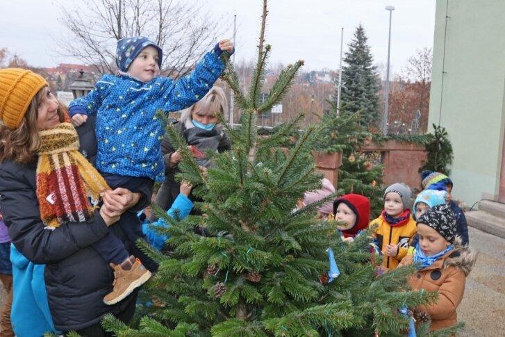 Kita-Gruppen schmücken Weihnachtsbäume vorm Rathaus