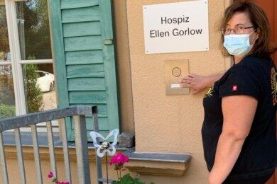 """Heike Bahndorf von der Physiotherapie Bahndorf & Lehnert läutet an der Eingangstür zum Hospiz """"Ellen Gorlow"""" in Oederan - mit Hilfe des Förderprogramms """"Lieblingsplätze für alle"""" war 2019 eine zusätzliche Klingel installiert worden."""
