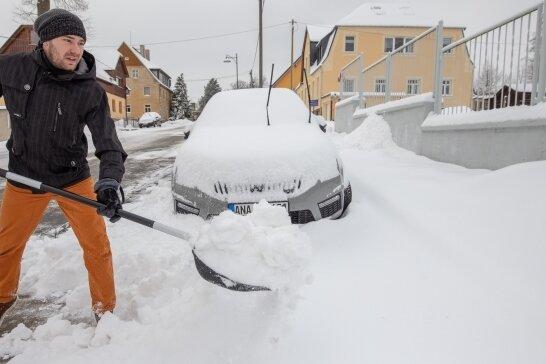 Erst in der Nacht zum Montag hat die Schneefront auch über dem Erzgebirge einiges der weißen Masse fallen lassen. So musste etwa Maik Garbe schaufeln, um das Auto freizulegen.