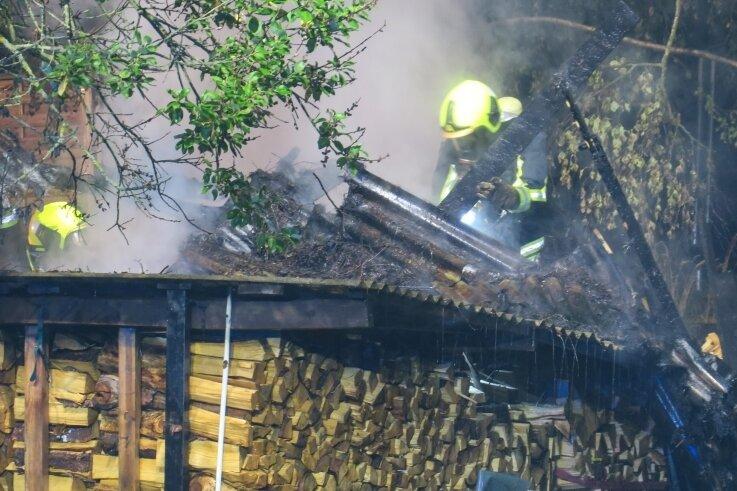 Das Feuer griff auf einen Schuppen und gelagertes Holz über. Das Löschen gestaltete sich für die Einsatzkräfte schwierig.