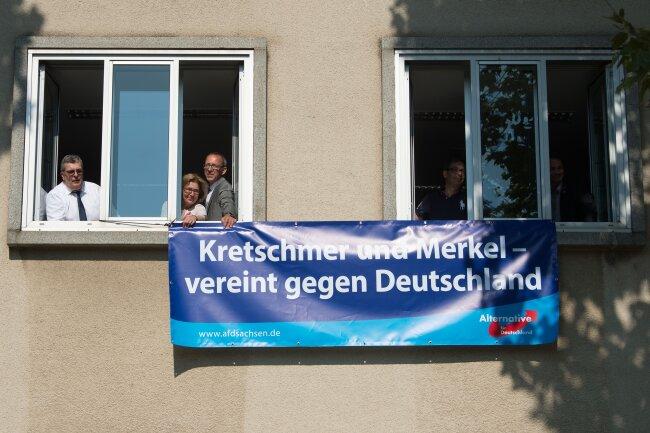 """Die AfD-Landtagsabgeordneten Carsten Hütter (v.l.n.r.), Karin Wilke, Jürg Urban, Andre Barth und Sebastian Wippel halten ein Plakat mit der Aufschrift """"Kretschmer und Merkel vereint gegen Deutschland""""."""