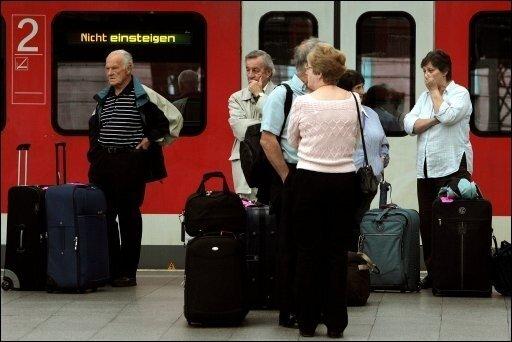 """Reisende stehen im Kölner Hauptbahnhof neben einem Regionalexpress, der """"Nicht einsteigen"""" anzeigt Bahnreisende bekommen jetzt mehr Rechte bei Verspätungen oder Ausfällen. (Archivfoto)"""