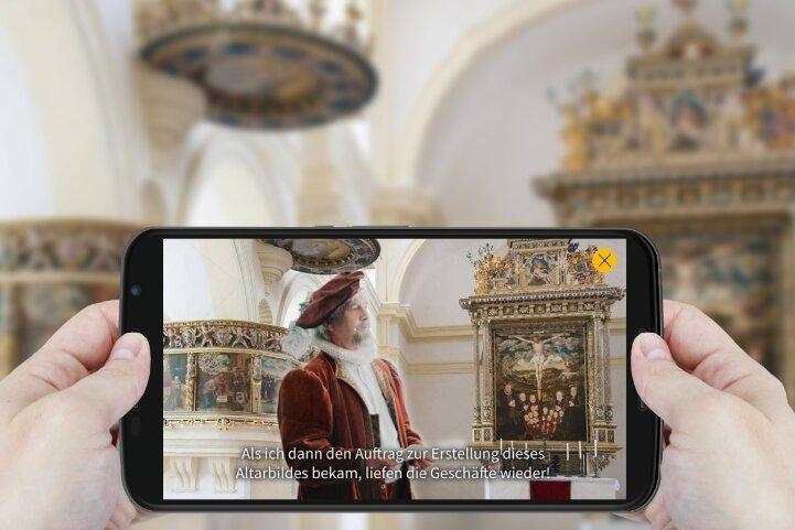 Wie hier bei einem Handy-Test in der Schlosskirche sehen die Besucher in den Kulissen Figuren auf ihrem Tablet.