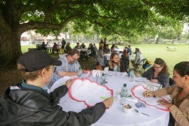 Insgesamt rund 70 Teilnehmer und Moderatoren tauschten sich an zwölf Tischen unter der Kaukasischen Flügelnuss im Stadthallenpark aus.