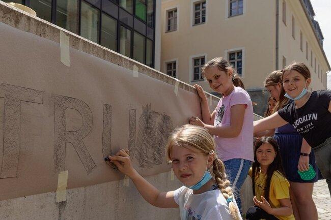 """Die graue Mauer vor dem Bildungszentrum """"Adam Ries"""" soll ein farbenfroher Blickfang werden. Schülerinnen der Klasse 4b gestalten ihn innerhalb eines Ganztagesangebotes unter Leitung von Sabine Sachs."""