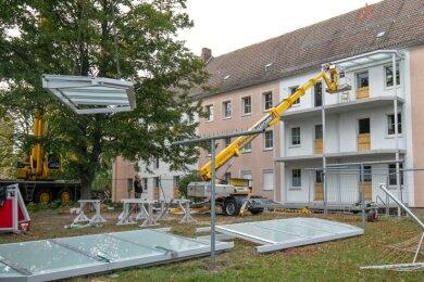 Bis Dezember haben die Balkonbauer an der Ringstraße zu tun. Dafür kommt auch ein Kran zwischen Wohnblöcken zum Einsatz.
