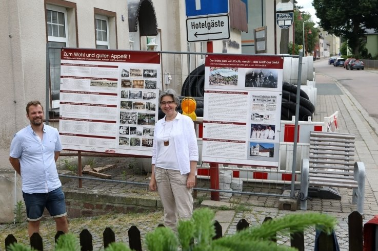 Patrick Bochmann, Leiter des Lichtensteiner Geschichtsvereins und Museumsleiterin Anne-Sophie Berner vor dem Rödlitzer Bauzaun.
