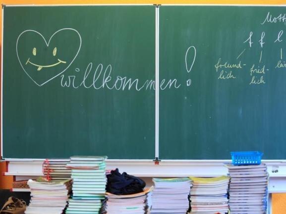 Willkommensgrüße stehen in einer Gemeinschaftsschule an der Tafel.