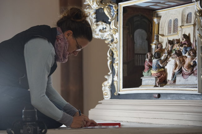 Restauratorin Anne-Kathrin Läßig dokumentiert ihre Arbeit am Altar der Stadtkirche in Mittweida.