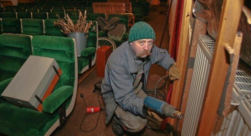 Jens Theska rückt dem eingefrorenem Heizkörper in Schneebergs Kino mit der Heißluftpistole zu Leibe.