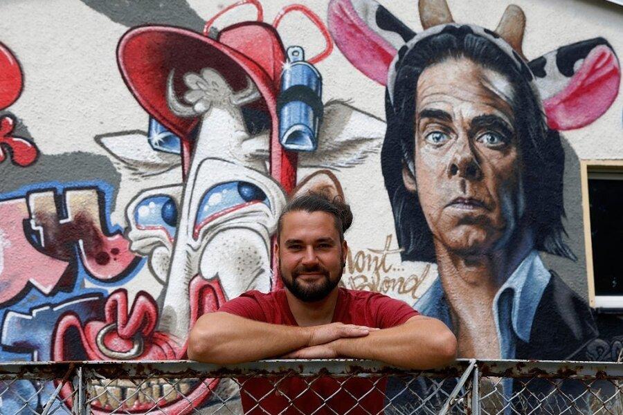 Tobias Winkler, Vorsitzender des Blinklicht-Vereins, an der mit Graffiti neugestalteten Fassade des Domizils an der Pappelstraße in Niederlungwitz.
