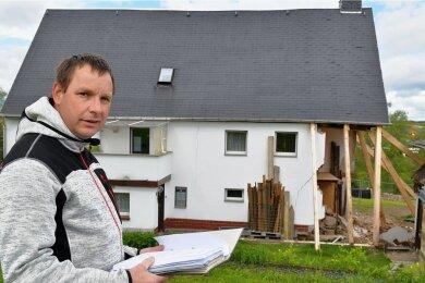 Frank Knüpfer aus Helbigsdorf vor seinem Wohnhaus, das durch das Technische Hilfswerk notgesichert wurde. Inzwischen liegt dem dreifachen Familienvater eine Teilbaugenehmigung vor. Voraussichtlich nächste Woche sollen Bagger den Bereich vorm Giebel ausbaggern, der dann umgehend mit Beton ausgegossen werden soll.
