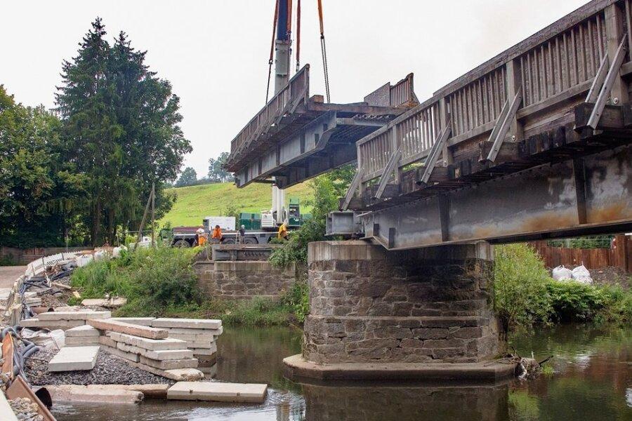 Es dauerte nicht lange, da hing das erste Teil der kaputten, alten Schönthalbrücke in Hennersdorf am Kranhaken und schwebte zum eigens eingerichteten Ablageplatz.