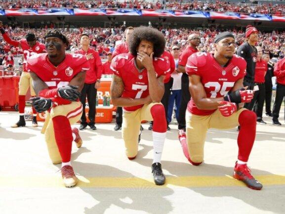 Colin Kaepernick (M.) kniete 2016 mit seinen Teamkollegen Eli Harold (l) und Eric Reid vor einem Spiel der San Francisco 49ers.