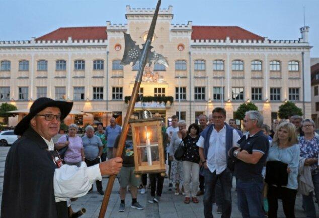 Christian Bretschneider (links) begrüßte als Nachtwächter bei seiner Tour gut 70 Personen. Dabei räumte er mit dem Irrglauben auf, Martin Luther habe einst vom Rathausbalkon (im Hintergrund) gesprochen.