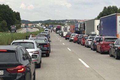 Nach einem Autobrand kommt es auf der A4 zu Stau. Autofahrer halten die Rettungsgasse ein.