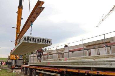 Mit einem Autodrehkran werden die Betonteile für die Decke des ersten Teils vom Rohbau des neuen Gemeindezentrums vom Schwerlasttransporter gehoben.