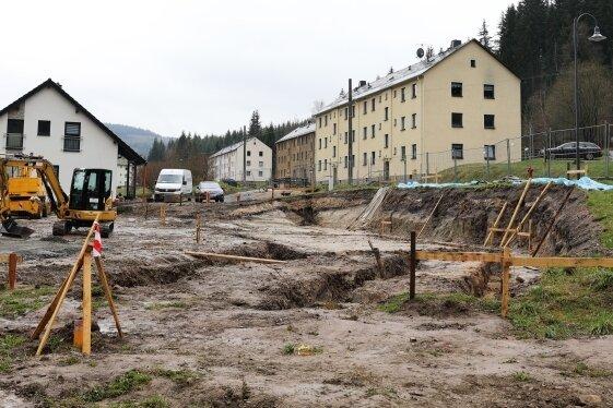 Ein im Mai 2021 entstandenes Bild mit Symbolcharakter: Rechts drei der alten Wohnhäuser der Milchbachsiedlung Erlabrunn, links ein neues Eigenheim und im Vordergrund die Fläche für ein weiteres Eigenheim.