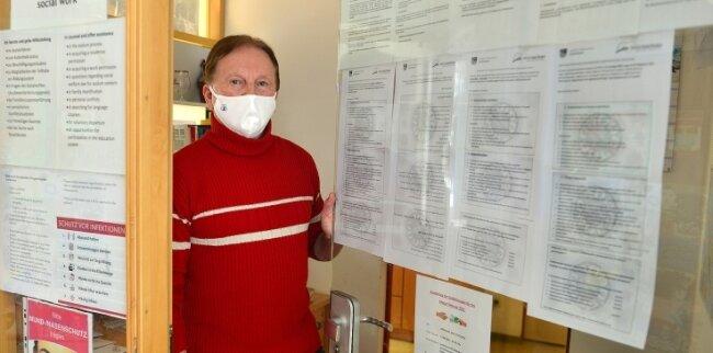 Heimleiter Dieter Weinberger zeigt die in der Asylunterkunft in Mobendorf ausgehängte Coronaverordnung in mehreren Sprachen.
