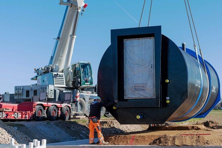 Mit dem Autokran wird die Druckerhöhungsanlage mit Saugbehälter neben der Straße zwischen Beedeln und Bernsdorf am für sie vorgesehenen Ort abgesetzt. Der Wasserverband investiert fast 300.000 Euro.