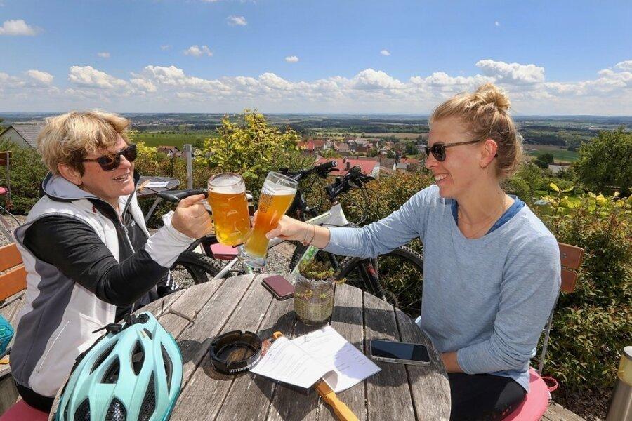 Prost! Mutter und Tochter machen während einer Radtour Halt in einem Biergarten in Uttenweiler-Offingen in Baden-Württemberg.