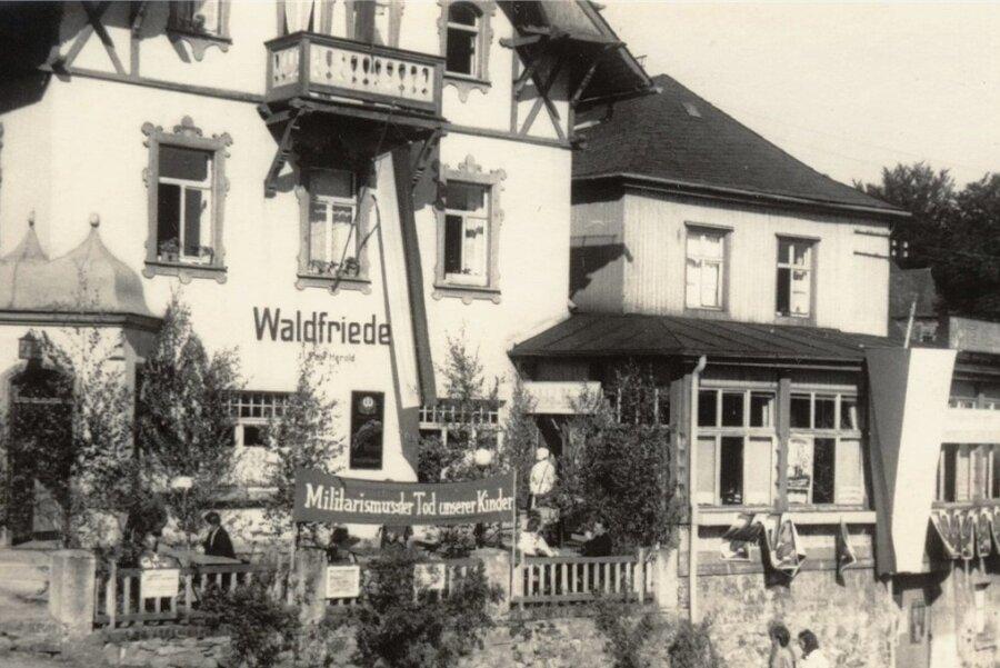 """""""Militarismus: Tod unserer Kinder"""". Eine Losung am Gasthaus """"Waldfriede"""" in Augustusburg, das im Juni 1946 Wahllokal für das sächsische Volksbegehren zur Enteignung von Industrieunternehmen, die Kriegsverbrechern und ehemaligen NS-Funktionären gehörten, war."""