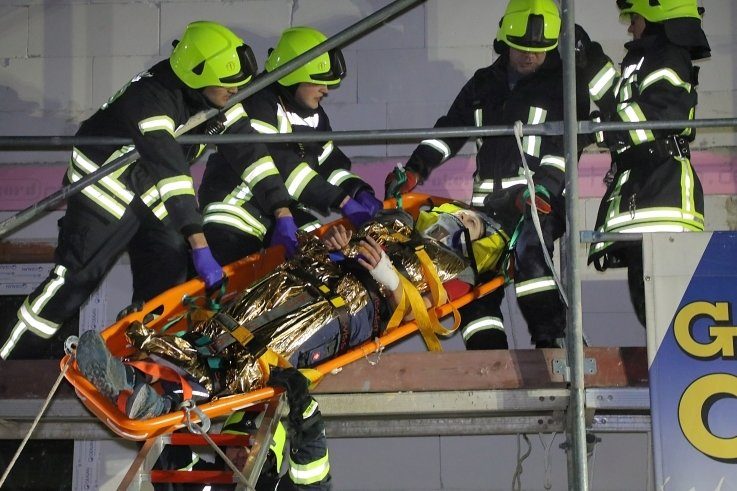 Harte Arbeit für die Feuerwehrleute: Die mit Seilen gesicherte Trage mit der verletzten Person muss auf die Leiter gezogen werden.
