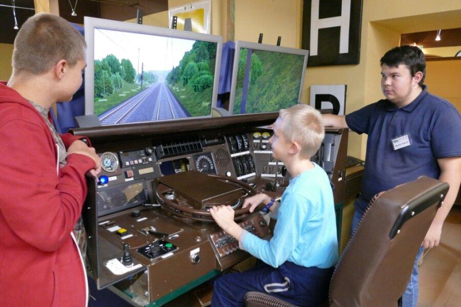 Die Brüder Maik und Ronny Zuschlag (von links) sind fasziniert von dem Cockpit samt Zugsimulator, an dem auch Martin Rösch (rechts) vom Zschopauer Modellbahnverein mitgebastelt hat.