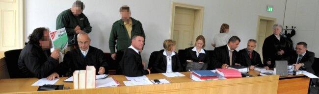 """<p class=""""artikelinhalt"""">Die extralange Anklagebank: Dort sitzen von links: Wolfgang G., der sich hinter einem Schreibblock verbirgt, und dessen Anwalt Bernd Behnke, Rechtsanwalt Andreas Redl, der Gina G. vertritt, sowie drei weitere Verteidiger. Ganz rechts hat Wolfgang G.s früherer Rechtsanwalt Thomas Höllrich als Angeklagter sozusagen am Katzentisch Platz genommen, neben ihm stehend seine Verteidigerin Rositha Sauer. </p>"""