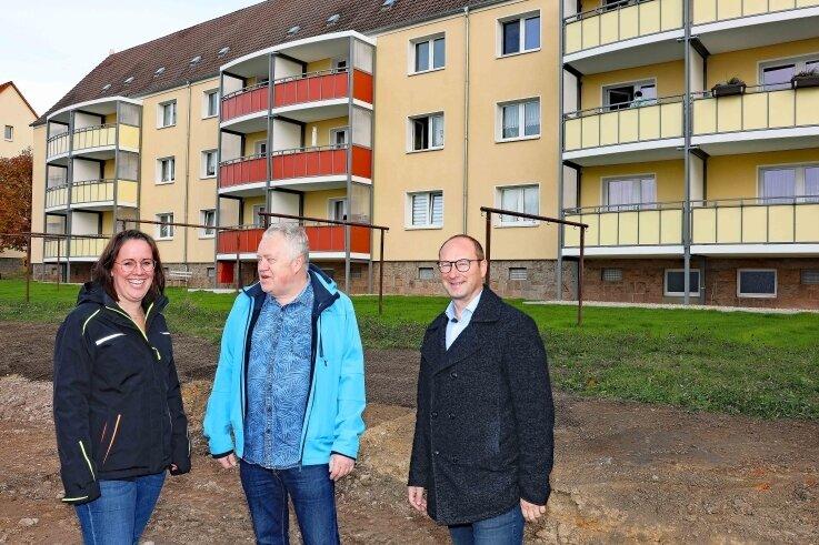 Peggy List und Carsten Bendier im Gespräch mit Mieter Bernd Sehrer (Mitte) vor dem modernisierten Wohnblock an der Holzstraße.