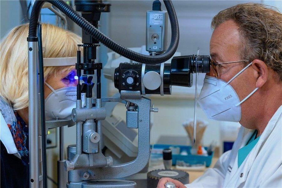 Mit Blaulicht macht Professor Lutz Pillunat einen vorab verabreichten Farbstoff im Auge von Susanne Balke sichtbar - und kann so den Augenhintergrund untersuchen.