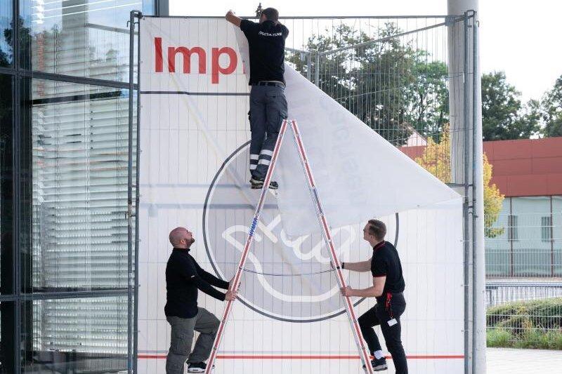 Arbeiter entfernen ein Transparent vor dem bisherigen Impfzentrum in Dresden.